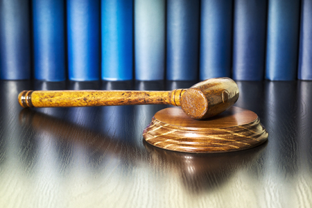 auction bid sale judgment mallet with unfocused books Stock Photo
