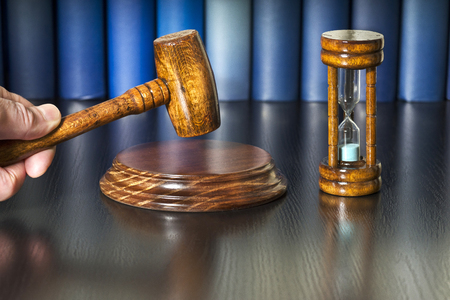 gavel mallet auction bid sale judgment with hourglass and books Stock Photo