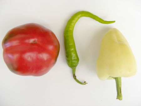 a green hot pepper with a red and a yellow paprika