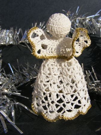 hand knitted angel on black background with silver decoration, christmas  Stock Photo
