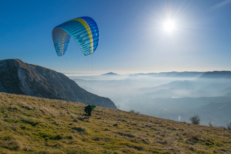 Paraglider launching on a mountintop with foggy valley, Icarus Stock Photo