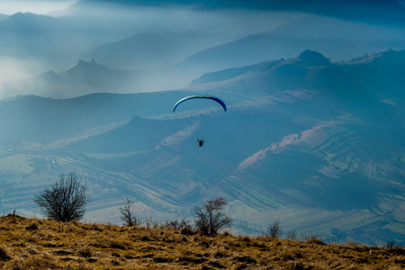 Paraglider, autumn landscape with foggy blue mountains in the background