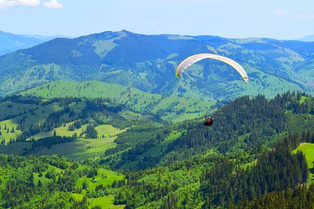 Paraglider over mountain pasture landscape,Transylvania