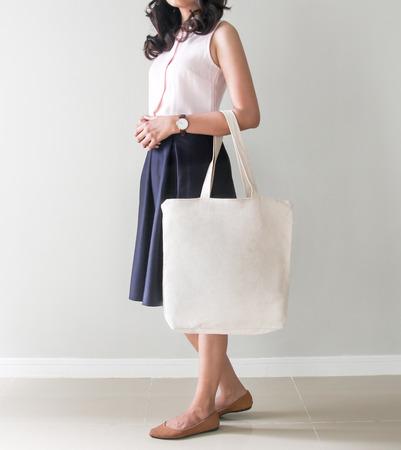 モックアップ。女の子は、空白のキャンバスのトートバッグを保持しています。女の子のための手作りエコ ショッピング バッグです。