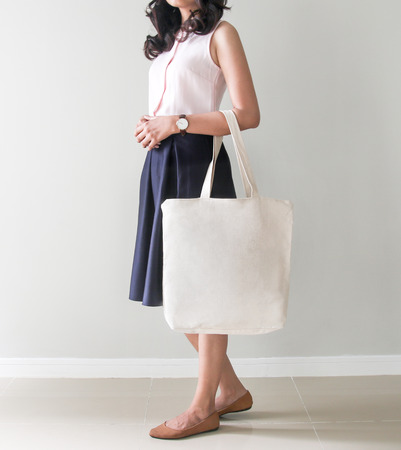 Mock-up. Girl is holding blank canvas tote bag. Handmade eco shopping bag for girls. Foto de archivo