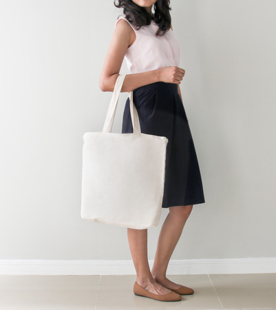 Mock-up. Girl is holding blank canvas tote bag. Handmade eco shopping bag for girls. Stock Photo