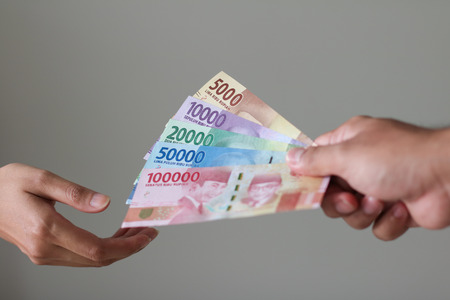 Man Hand give Indonesian Money Rupiah Stock Photo