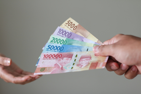 Man Hand give Indonesian Money Rupiah Stock Photo