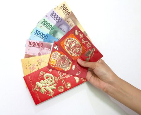 Chinese new year envelope with Indonesian rupiah money in hand Stock Photo