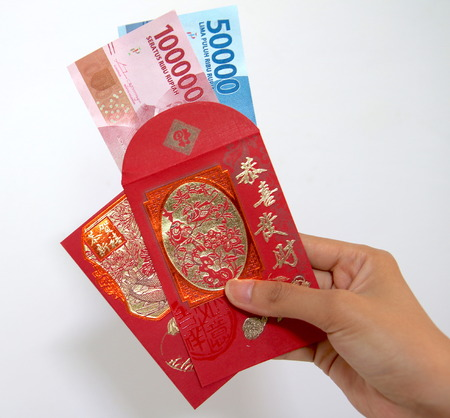 Chinese new year envelope with Indonesian rupiah money in hand Banco de Imagens