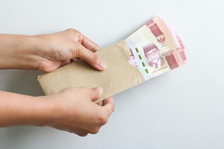 hand holding rupiah Indonesian money on brown envelope Banco de Imagens