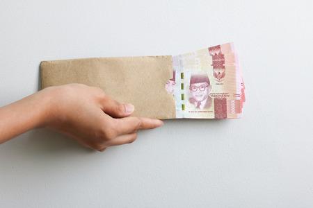 hand holding rupiah Indonesian money on brown envelope Imagens