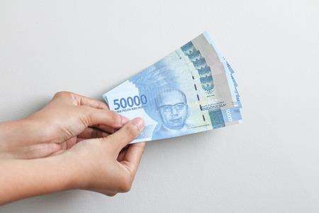 hand holding rupiah Indonesian money Banco de Imagens