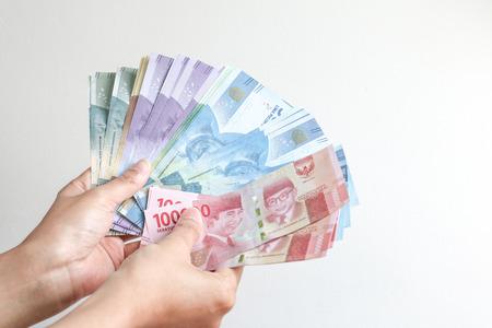 hand met Roepie Indonesisch geld