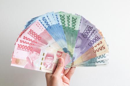 hand holding rupiah Indonesian money Фото со стока
