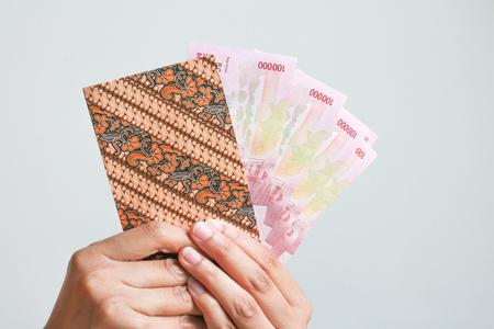 봉투에 인도네시아어 돈 루피아를 게재하는 여자 손