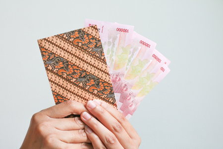 Woman Hand showing Indonesian Money Rupiah on envelope