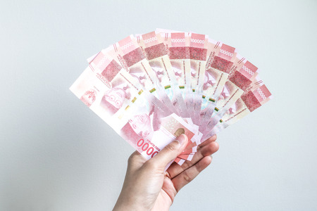 hand holding rupiah Indonesian money Stock Photo