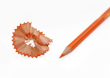 sharpenings: Orange pencil and shavings on white background