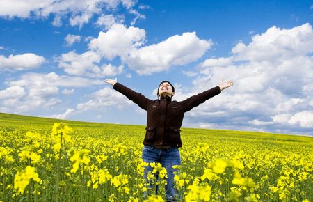 Young attractive girl having fun in summer rape field photo