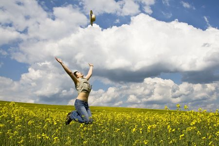 Young attractive girl jumping in rape field and throwing straw hat photo