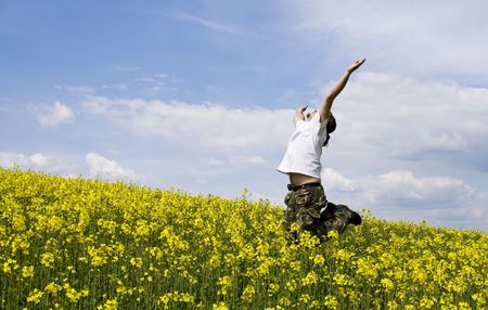 Young attractive man jumping in summer field photo
