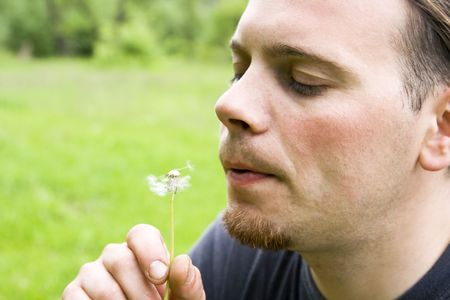 blow up: Young man blowing dandelion against green background