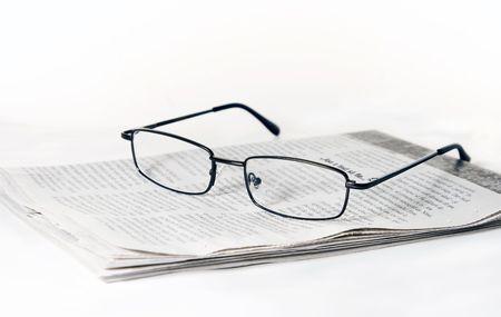 Glasses on folded newspaper photo