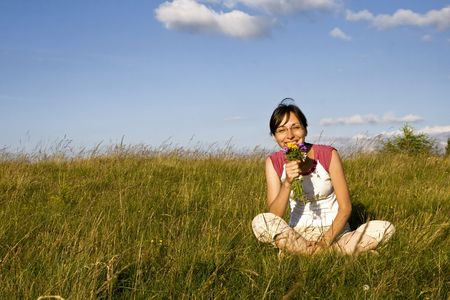 Young woman with wild flowers in meadow Stock Photo - 3275126