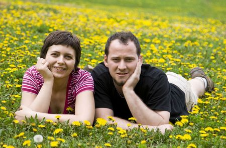 giggle: Couple laying in a meadow full of dandelions