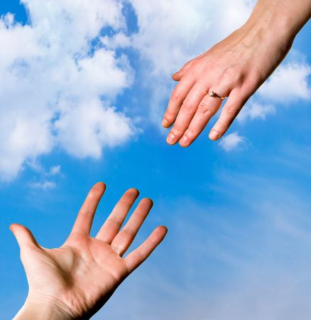 Man and womans hands reaching for each other against blue sky photo