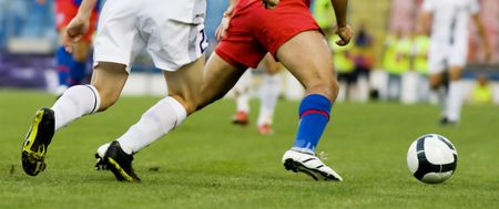 soccer match: Soccer players running after the ball