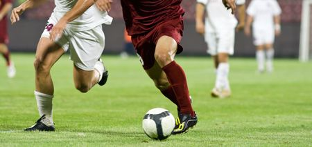 Soccer players running after the ball