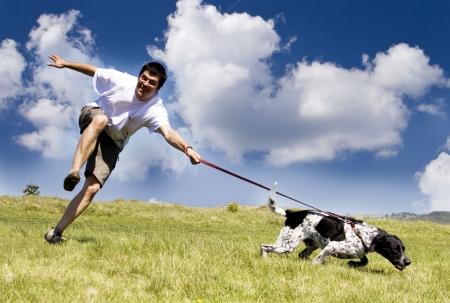 perro corriendo: Hombre jugando con su perro en día soleado de verano