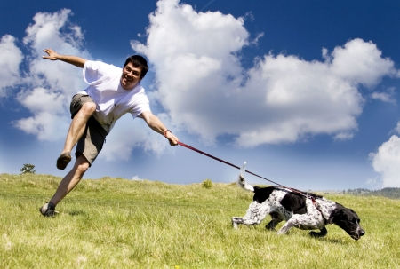 dog running: Man playing with his dog on sunny summer day Stock Photo