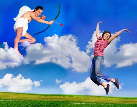 Flying Cupid aiming his bow at young happy woman photo