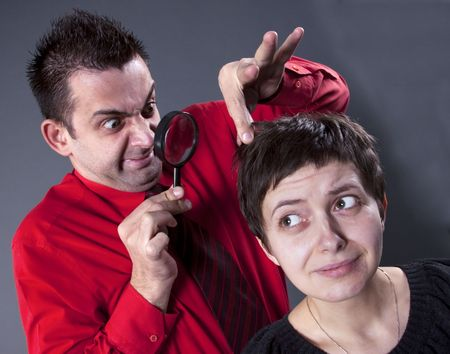 woman's: Man examining womans hair with magnifying glass Stock Photo