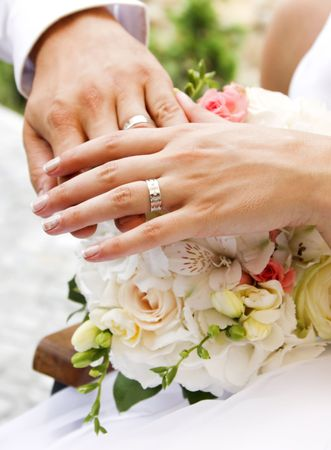 Hands and rings on wedding bouquet  photo