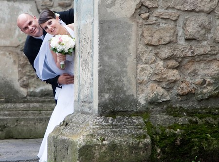 Beautiful bride and groom posing among old church walls  Stock Photo - 7354338