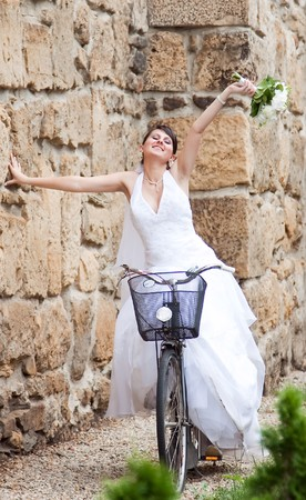 Happy bride riding a bike photo