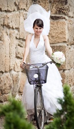 trash the dress: Happy bride riding a bike