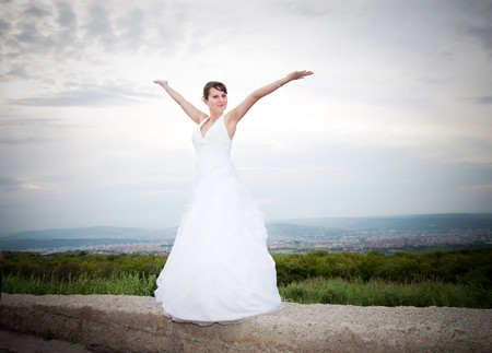 Happy bride with arms open against blue sky  Stock Photo - 7348000