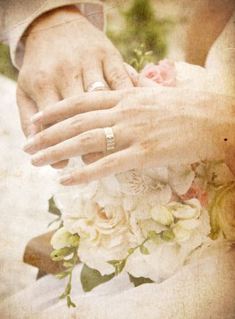 Vintage card with hands and rings on bridal bouquet photo