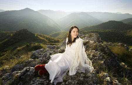 Beautiful bride posing on rocks in high mountain scenery photo