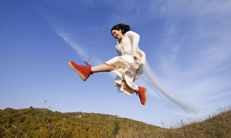 Happy bride with red boots jumping high photo