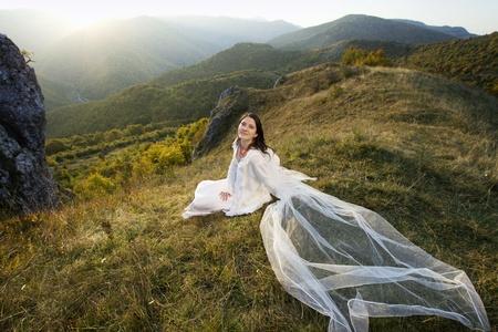 Beautiful bride posing in high mountain scenery  photo