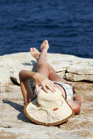 sun bathing: woman with hat sunbathing on rocks near big waves