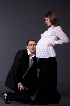Happy young man and his pregnant wife isolated on white  photo
