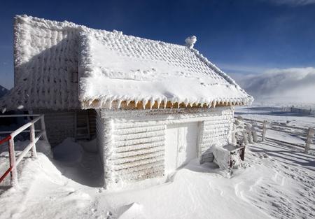 cabina: Casa de madera cubierta de nieve en las monta�as  Foto de archivo