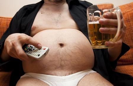 ubriaco: Sovrappeso uomo seduto sul divano con un bicchiere di birra e controllo remoto  Archivio Fotografico